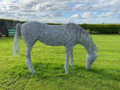 55. Life-size grazing horse sculpture in cloudscape, 20