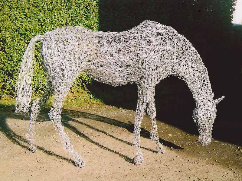 23. Wire grazing horse against black and green