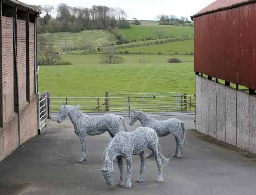 22. Three wire horses with green fields in the distance