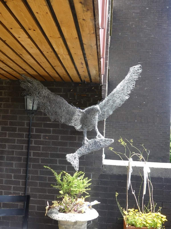 55. Eagle in flight, wire eagle and fish sculpture on the balcony.